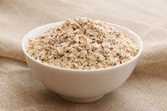 Bowl of Oats. Scottish porridge oats in a white cereal bowl on a burlap background royalty free stock photos