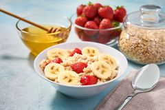 Bowl Of Oatmeal Porridge With Banana And Strawberry On A Turquoise Background. Delicious And Healthy Food For Breakfast Stock Image