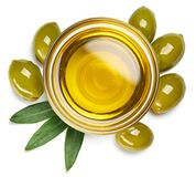 Bowl of olive oil and green olives with leaves Royalty Free Stock Photos