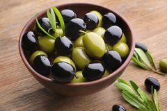 Bowl with olives on table. Bowl with olives on wooden table royalty free stock images