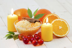 Bowl of orange bath salt with fresh fruits Stock Image