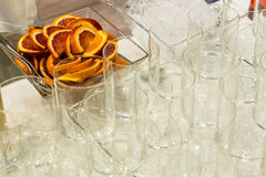 Orange slices. Bowl of orange slices and glasses on a buffet table Royalty Free Stock Photo