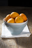 Bowl of Oranges on a rustic wooden table Stock Photo