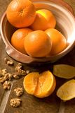 Bowl of oranges on Spanish tile floor. Natural light image of stillife with oranges and walnuts Stock Photos