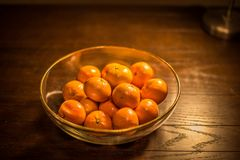 Bowl of oranges on wooden table Royalty Free Stock Images