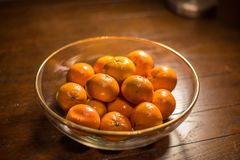 Bowl of oranges on wooden table Stock Image