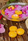 Bowl with orchids and candle on wooden table Stock Image