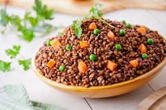 Bowl Of Organic Lentils With Carrot And Peas. Close up of some organic brown lentils Stock Images