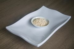 Bowl of organic pearl barley on white plate Stock Photo