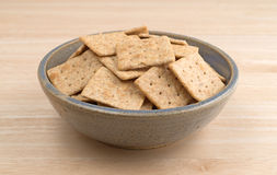 Bowl of organic whole wheat crackers on a wood table Stock Photo