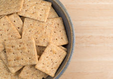 Bowl of organic whole wheat crackers on a wood table Royalty Free Stock Photo
