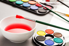 Bowl with paintbrush and set of watercolors Stock Photos