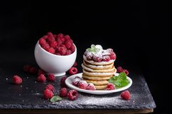 Bowl and Pancakes with raspberries around on black backgound Royalty Free Stock Image