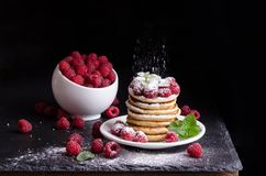 Bowl and Pancakes with raspberries around on black background. Bowl and Pancakes with raspberries around on black stone background Stock Image