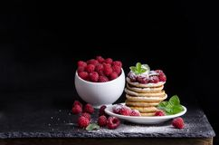 Bowl and Pancakes with raspberries around on black background. Bowl and Pancakes with raspberries around on black stone background Stock Images