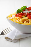Bowl of pasta with tomato sauce and fresh basil Stock Photo