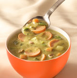 Bowl of pea soup. Bowl on a table with pea soup and a spoon hovering above Royalty Free Stock Photo