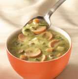 Bowl of pea soup. Bowl on a table with pea soup and a spoon hovering above Stock Photography