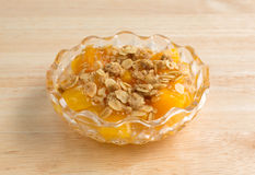 Bowl of peaches with brown sugar and oats on wood table Royalty Free Stock Images