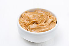 Bowl of peanut butter on white wooden table Stock Photo