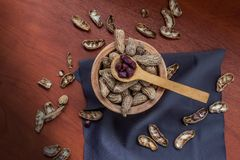 Aerial shot of peanut bowl with shell, some are peeled next to a wooden spoon royalty free stock image