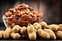 Bowl with peanuts on wooden table. Royalty Free Stock Images