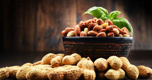 Bowl with peanuts on wooden table. Stock Photos