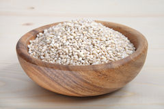 A bowl of pearl barley on wooden surface Stock Images
