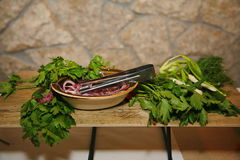 Bowl with pickled onions and steel Cutlery tongs, and edible herbs on a wooden shelf stand. Royalty Free Stock Photos