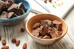 Bowl with pieces of delicious dark chocolate. On wooden table royalty free stock photo