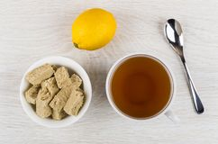 Bowl with sunflower halva, lemon, cup of tea and spoon. Bowl with pieces of sunflower halva, lemon, cup of tea and spoon  on wooden table. Top view Royalty Free Stock Images