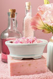 Bowl of pink sea salt, bar of handmade soap and bottle of liquid Stock Photo