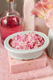 Bowl of pink sea salt, bar of handmade soap and bottle of liquid Royalty Free Stock Photo