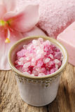 Bowl of pink sea salt and lily flower in the background Royalty Free Stock Images