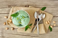 Bowl of pistachio ice cream, overhead still life on wood. Bowl of pistachio ice cream, overhead still life on a wooden background Royalty Free Stock Photography