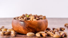 Bowl of pistachio nuts wood floor Royalty Free Stock Photography