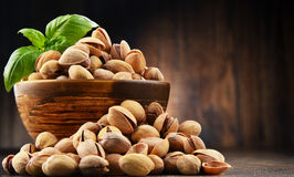Bowl with pistachio on wooden table Royalty Free Stock Photos