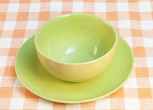 Bowl and plate on checkered tablecloth Stock Image
