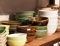 Bowl and plate in many shapes ceramic pottery clay stacked in store shelf hand made craft collection view from top Royalty Free Stock Image