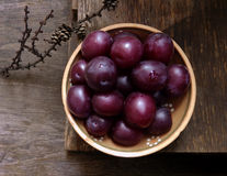 Bowl with plums, top view, on a wooden background Stock Photos