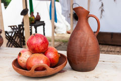 Bowl of pomegranate fruits and earthenware pitcher Stock Photography