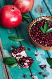 A bowl of pomegranate seeds. On the old wooden background. Rustic still life Stock Images