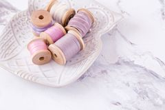 Bowl with pool of threads over marble table Royalty Free Stock Photos