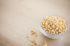 Bowl of pop corn kernels on wooden table. Bowl of raw pop corn kernels on wooden table Royalty Free Stock Photography
