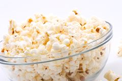 Bowl of popcorn. Closeup of glass bowl of popcorn with few peaces throw around stock photography