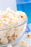 Bowl of popcorn. Closeup of glass bowl of popcorn and bottle of sparkling water in background stock photo