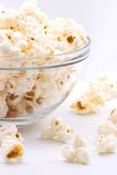 Bowl of popcorn. Closeup of glass bowl of popcorn with few peaces throw around stock images