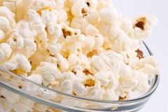 Bowl of popcorn. Closeup of glass bowl of popcorn with few peaces throw around stock photo