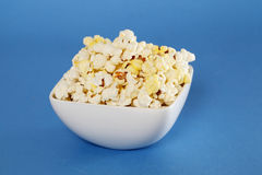 Bowl of popcorn on blue Stock Photos