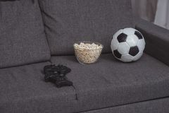 bowl with popcorn, football ball and gamepads royalty free stock photo
